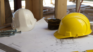 Two hard hats sitting on top of blueprints at construction site.