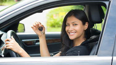 Auto Loan - Woman smiling sitting in car holding up car key.