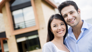 Smiling couple with arms around one another in front of house.