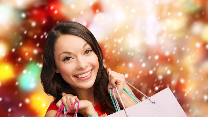 Young woman smiling holding shopping bags with snowflakes in background.