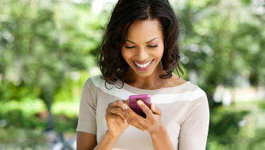 Woman standing outside smiling and looking at smartphone.