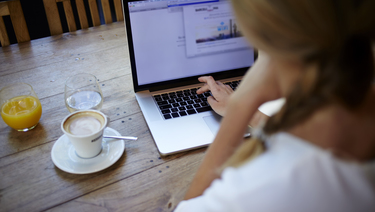 Woman working on laptop at kitchen table with cup of coffee and glass of orange juice.