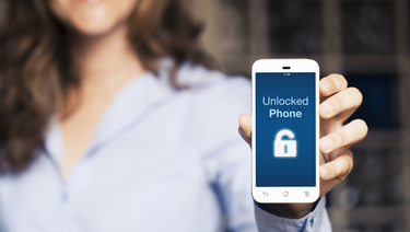 "Woman holding smartphone that reads ""Unlocked Phone"" with unlocked padlock icon on the screen."