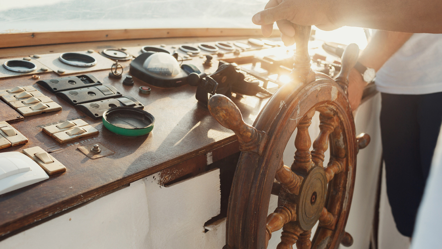 Hand on ship steering wheel or helm, with navigation gauges and tools on dashboard.