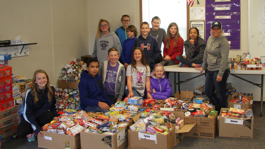 Group on children with teacher surrounded by boxes of non-perishable foods for the 2018 Kick Childhood Hunger Food Drive.