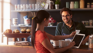 Male barista with beard and glasses standing behind counter while brunette woman with ponytail uses credit card to pay at Bank of Utah merchant services card reader.