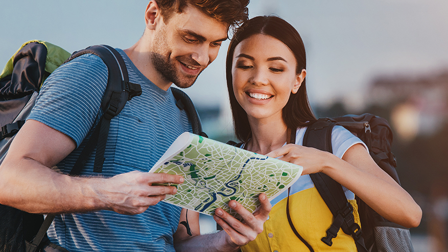 A man and a woman wearing backpacks looking at a map